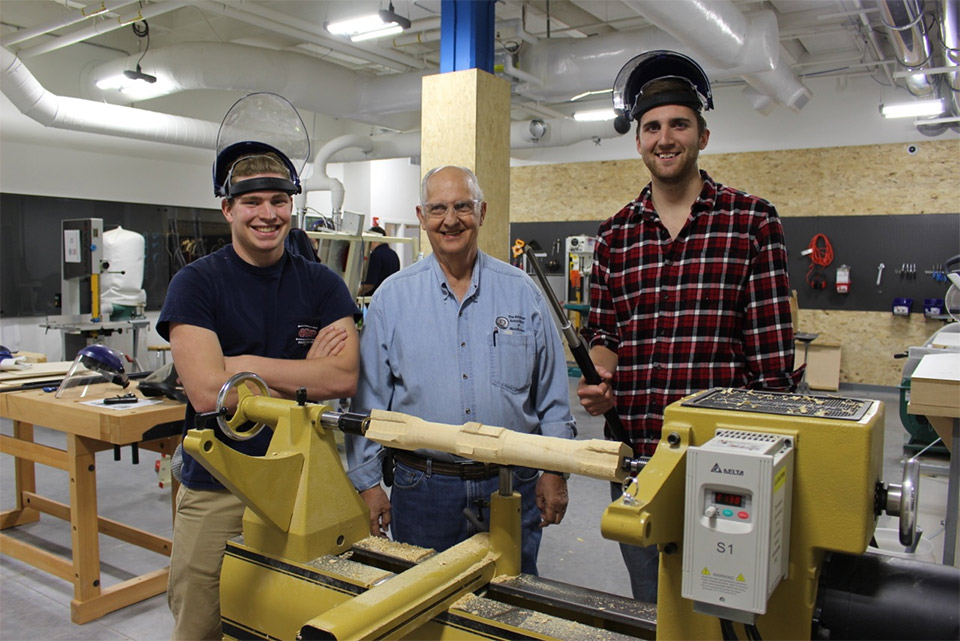 Students and woodturner teacher in shop